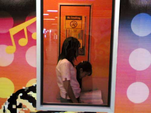 2 girls in coin operated karaoke booth