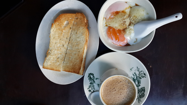 typical 1 Malaysia breakfast with toast, half boiled eggs, coffee - food shot