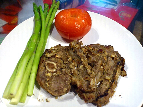lamb chop with tomato and asparagus on the side